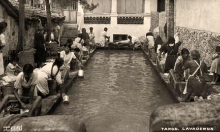 sw Foto: Frauen rund um ein Wasserbecken waschen kniend an steinernen Podesten mit Wassermulden und schräger Waschfläche