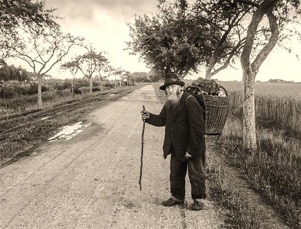 sw Foto: alter Mann mit Besen im Tragekorb zu Fuß unterwegs auf einer Landstraße