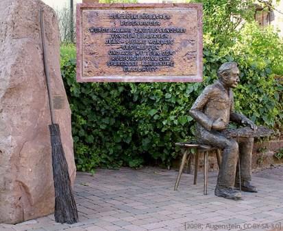 Bronzefigur: auf Hocker sitzender Besenmacher zurrt Seil um Ruten fest, links daneben großer Sandstein mit Stiftungstafel und angelehntem Bronzebesen