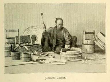 Mann sitzt am Boden, hält die Nägel mit seinen Zehen und baut ein Fass