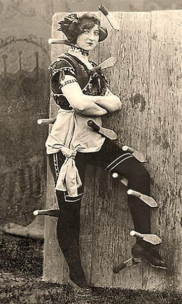 sw Foto: Frau in Profilposition vor Zielbrett zwischen Messern