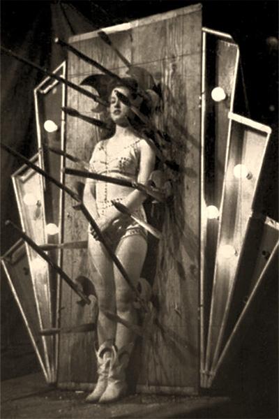 sw PK: Frau vor beleuchtetem Zielbrett zwischen Messern und Äxten