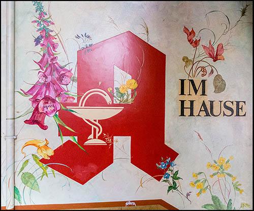 floral verziertes Apothekerzeichen in einem Hausflur