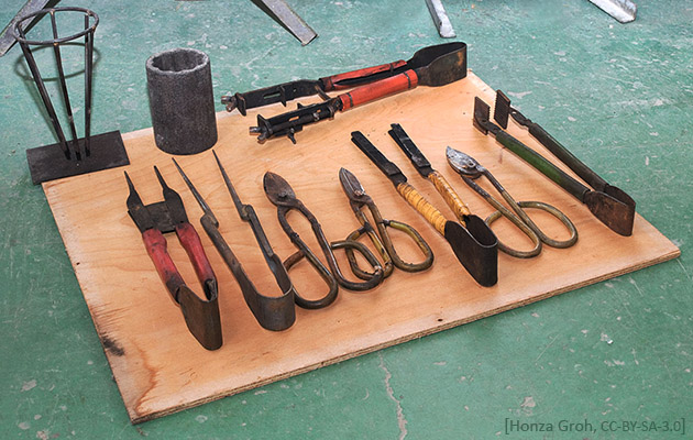 Farbfoto: u.a. Glasbläser-Scheren, -Pinzetten, -Strukturzangen auf einem Holzbrett