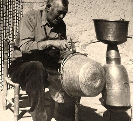 sw Foto: älterer Kesselschläger bearbeitet im Freien sitzend einen Henkelkessel