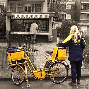 Farbfoto: Zustellerin mit Postrad am Straßenrand