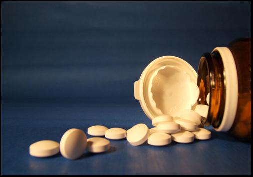 weiße Tabletten, die aus einem Glas rausrollen