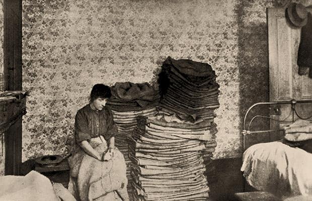 sw Foto: arme Frau flickt Säcke in ihrer Wohnkammer