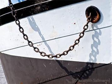 Farbfoto: aus Boot heraus hängende Kette