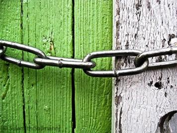 Farbfoto: silberne Vorhängekette an Holztür