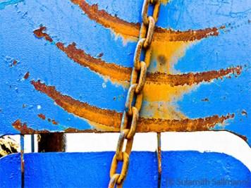 Farbfoto: rostige Kette an zerschrammtem Eisenblech