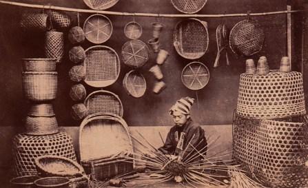 altes Foto: Mann sitzt zwischen fertigen Körben und arbeit an einem Korb