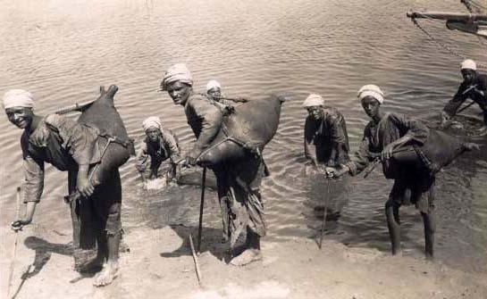 altes sw-Foto: sieben Wasserträger schöpfen Wasser aus einem Gewässer