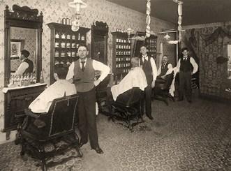sw Foto: drei Friseure mit vor Spiegeln sitzenden Kunden im Herrensalon -1905
