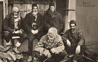 sw Postkarte: Gruppenfoto von fünf bei Gepäck sitzenden Trägern