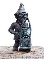 kleine Bronzefigur mit Zipfelmützeund Gepäckkarre