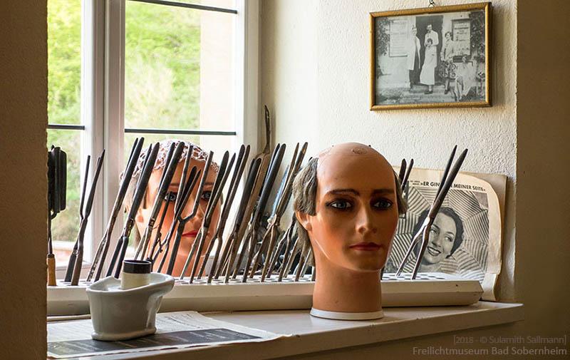 Farbfoto: diverse alte Friseurutensilien im Fenster der Friseurstube