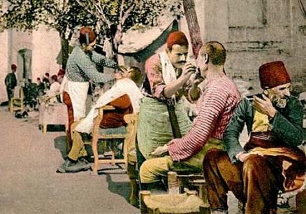 Postkarte: Männer lassen sich am Straßenrand balbieren und frisieren - 1900