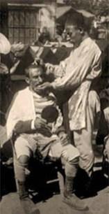sw Foto: Straßenfriseur bedient Mann mit Handspiegel - 1910