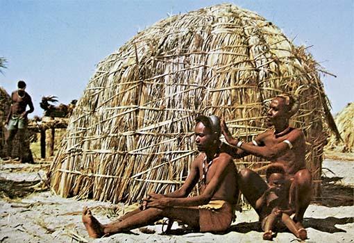 Farbfoto: Suk frisiert einen im Sand sitzenden Mann vor Strohhütte