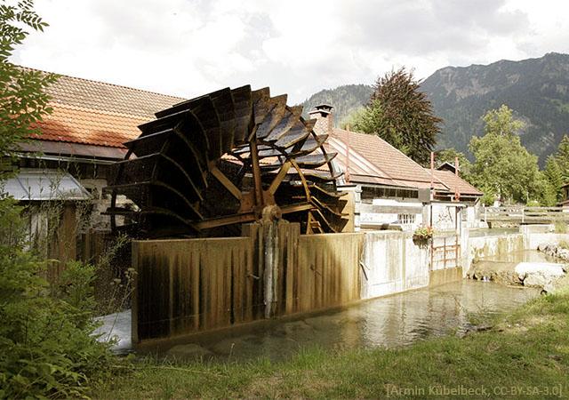 Farbfoto: großes Wasserrad vor der Schmiede am Wasserlauf