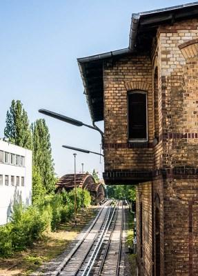 Farbfoto: altes Gebäude und vorbeiführende Schienen