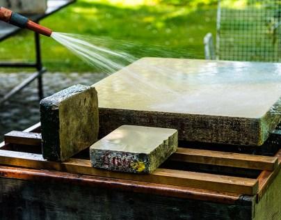 mit Wasserschlauch wird der Druckstein abgespült