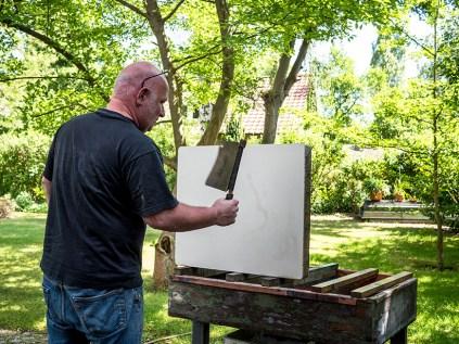 Der Steindrucker trocknet mit einem Pappwedel den Stein