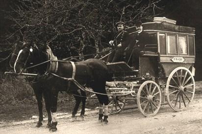 sw Foto: Kutscher und Fahrgast auf dem Kutschbock sitzend bei Fahrt durch den Wald