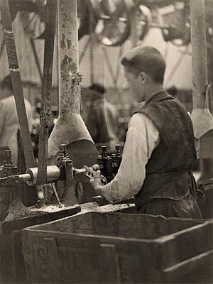 sw Foto: junger Knopfmacher arbeitet an einer Maschine