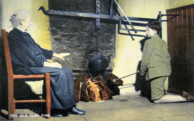 Junge macht Feuer aus Torfstücken, um Kessel zu zu erhitzen, alte Frau wärmt sich nebendran