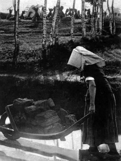 sw-Foto: Frau schiebt einfachen Karren mit Torfstücken