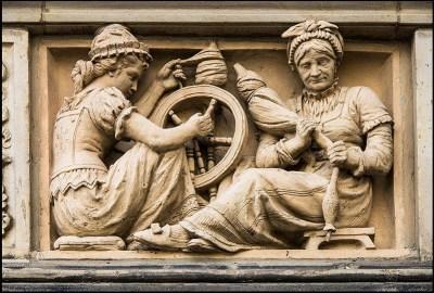 Lehmrelief: junge und alte Frau am Spinnrad