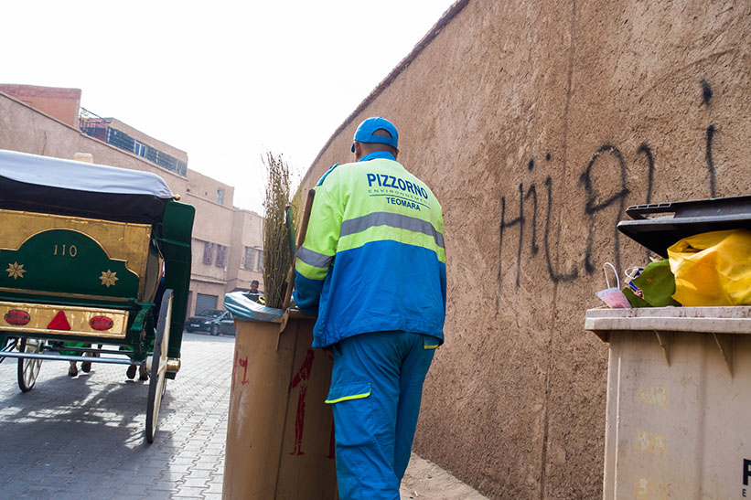 Straßenkehrer mit leerer Mülltonne und Besen