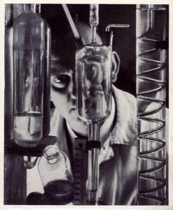 Sammelbild, Foto: Mann schaut durch gläserne Laborgeräte