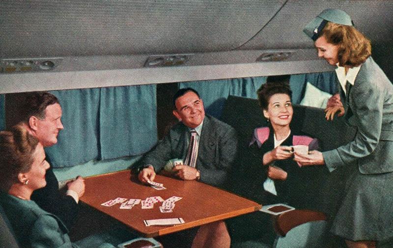 farbige Postkarte: Stewardess bringt kartenspielenden Passagieren Tasse Kaffee