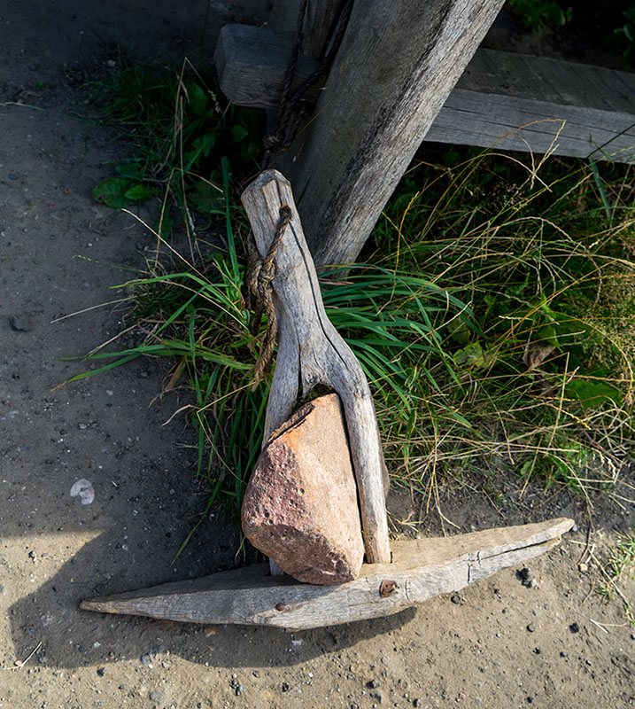 Anker aus Holz mit einem Stein als Gewicht