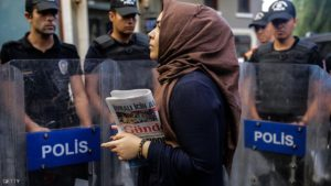 "A woman holds a ""Ozgur Gundem"" newspaper in front of a police barricade on August 16, 2016 in Istanbul.  A Turkish court has ordered the temporary closure of a newspaper accusing it of links with Kurdish militants and spreading terrorist propaganda. / AFP / YASIN AKGUL        (Photo credit should read YASIN AKGUL/AFP/Getty Images)"