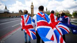 TOPSHOT - People walk over Westminster Bridge wrapped in Union flags, towards the Queen Elizabeth Tower (Big Ben) and The Houses of Parliament in central London on June 26, 2016.  Britain's opposition Labour party plunged into turmoil Sunday and the prospect of Scottish independence drew closer, ahead of a showdown with EU leaders over the country's seismic vote to leave the bloc. Two days after Prime Minister David Cameron resigned over his failure to keep Britain in the European Union, Labour leader Jeremy Corbyn faced a revolt by his lawmakers who called for him, too, to quit.  / AFP / Odd ANDERSEN        (Photo credit should read ODD ANDERSEN/AFP/Getty Images)