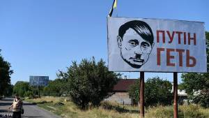 """A villager walks past an Ukrainian flat and a bilboard and despicting Russian president Vladimir Putin bearing a Hitler moustache and haircut, on August 26, 2014 in Volnovakha  near Donetsk. (Placard reads: """"Putin Go Away""""). AFP PHOTO/ FRANCISCO LEONG        (Photo credit should read FRANCISCO LEONG/AFP/Getty Images)"""
