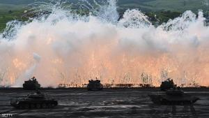 Japanese Ground Self-Defense Force tanks move amongst an umbrella of barrage during an annual live fire exercise at the Higashi-Fuji firing range in Gotemba, at the foot of Mount Fuji in Shizuoka prefecture on August 18, 2015. The annual drill involves some 2,300 personnel, 80 tanks and armoured vehicles and some 20 aircraft and helicopters.   AFP PHOTO / Toru YAMANAKA        (Photo credit should read TORU YAMANAKA/AFP/Getty Images)