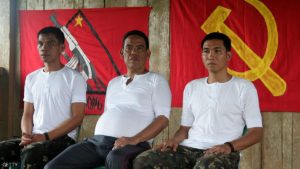 Mayor of Mindanao's Lingig town Henry Dano (C) his two soldier escorts Private First Class Allan Saban (L) and Corporal Alrey Desamparado (R) sit as they are presented to the media by their captures members of the Philippine communist rebel group the New People's Army (NPA) in the Caraga region of the insurgency-wracked southern Philippine Mindanao island on October 9, 2011, before their release. The town mayor and his two military escorts were released after more than two months in captivity, a day after the rebels also released four jail guards, the military said. AFP PHOTO (Photo credit should read STR/AFP/Getty Images)