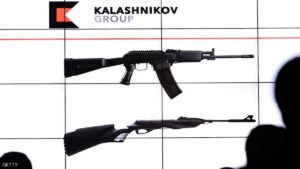 "People look at the screen during the presentation of the new logo of the Kalashnikov company in Moscow on December 2, 2014. The legendary Russian weapons manufacturer Kalashnikov hit by US sanctions, Tuesday presented its new logo to ""promote more effectively"" products, whose most famous rifles in the world AK-47. The logo executed in red and black - the colors of the flag of Udmurtia (Urals) where are the main plants of the company Kalashnikov - represents a large letter ""K"" like in shape to the charger AK-47. AFP PHOTO / VASILY MAXIMOV        (Photo credit should read VASILY MAXIMOV/AFP/Getty Images)"