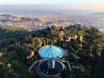 Barcelona, Spain – December 31, 2019: Barcelona panorama from Tibidabo hill. In the foreground, Tibidabo Theme Park, and Barcelona city and the coast line in the background.
