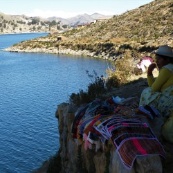 Isla del Sol, Bolivia– August 22, 2013: A woman dressed in a traditional outfit sells textile crafts.