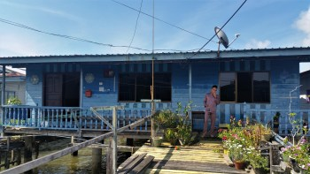 Kampong Ayer, Brunei – July 17, 2015: A man dressed in traditional outfit smokes in front of a blue house over the water in Kampong Ayer, a historic settlement area in Bandar Seri Begawan made of a cluster of traditional stilt villages built on the Brunei River.