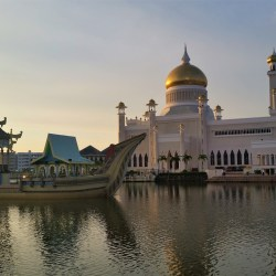 Bandar Seri Begawan, Brunei – July 17, 2015: Façade of Omar Ali Saifuddien Mosque at sunset. The mosque unites Mughal architecture and Malay styles. It's built in an artificial lagoon on the banks of the Brunei River at Kampong Ayer.