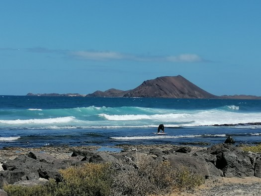 A surfer in front of Isla de Lobos captured from Corralejo