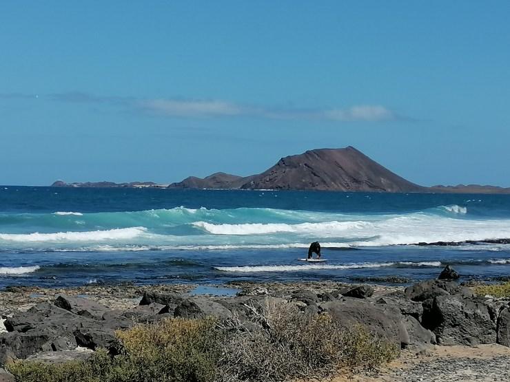 A surfer in front of Isla de Lobos captured from Corralejo