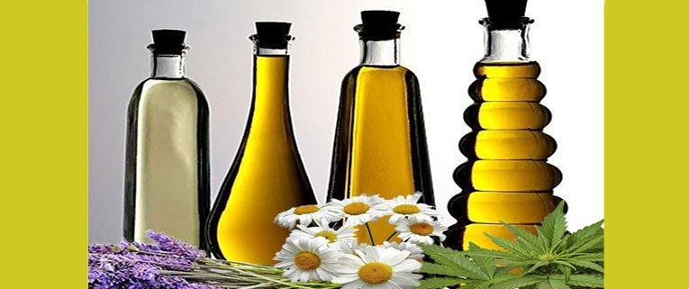 essential oils - 4 bottles of oil with lavender, daisies and cannabis flowers below